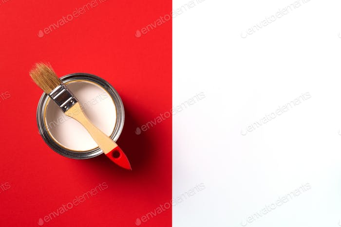 Wooden paint brush, open paint can on trendy red and white background. Top view, copy space