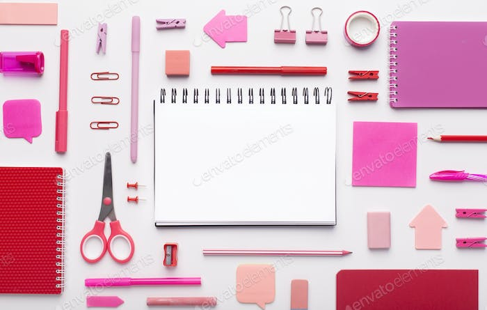 Notepad with blank space surrounded by pink office supplies