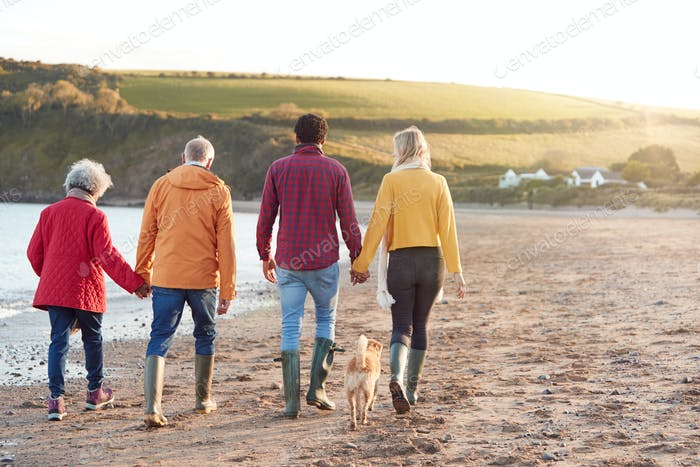 Senior Couple Hold Hands As They Walk Along Shoreline With Adult Offspring On Winter Beach Vacation