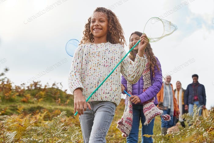 Multi-Generation Family Walking Through Countryside Carrying Fishing Nets On Winter Beach Vacation