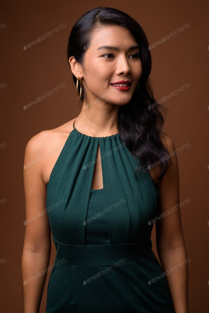 Studio shot of beautiful Asian businesswoman in green dress