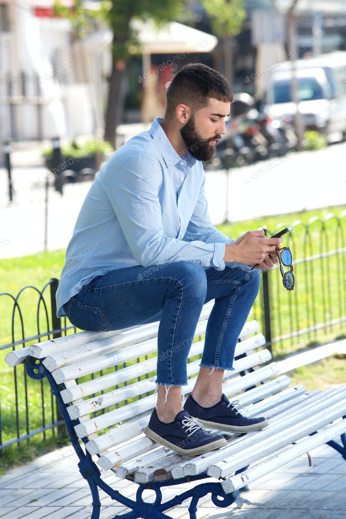 Full body handsome man sitting on bench with mobile phone