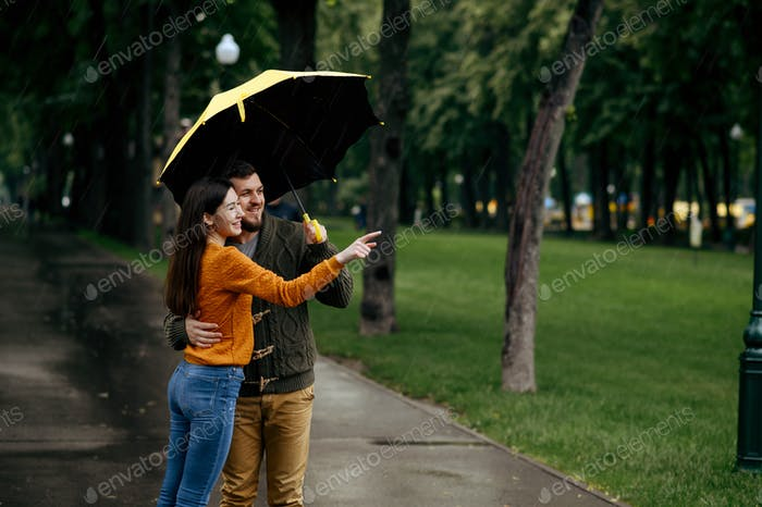 Happy love couple leisures in park, rainy day