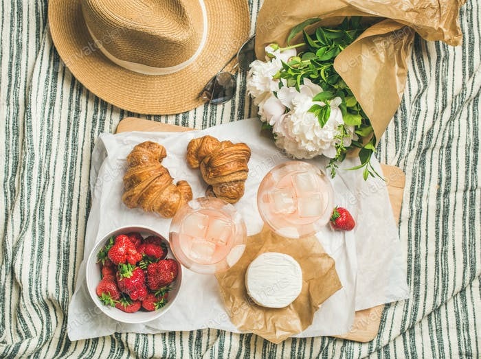 Flat-lay of glasses of rose wine, strawberries, croissants, brie cheese