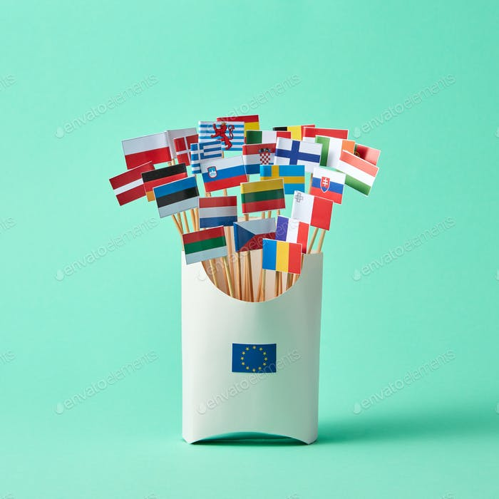Set of different paper flags in cardboard box decorated with EU sign on green background with copy