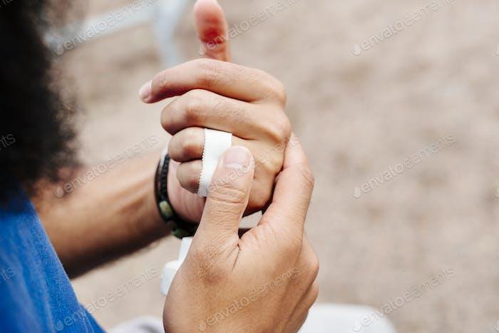 Man applying adhesive bandage to hand