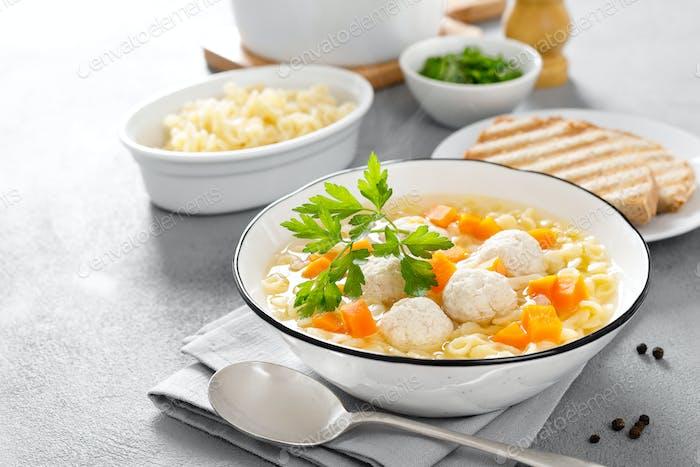 Heiße Hühnersuppe, Brühe mit Fleischbällchen, Karotten, Nudeln und frischer Petersilie