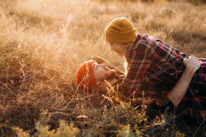 Chico alegre y chica en un paseo en sombreros de punto brillantes