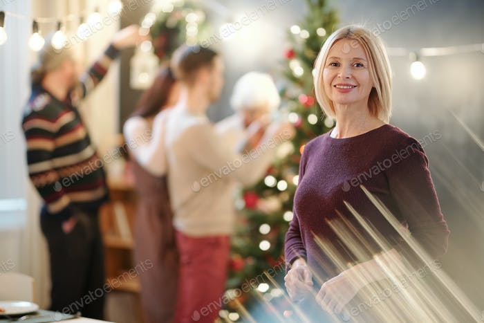 Mature blonde woman wishing you merry Christmas in front of camera