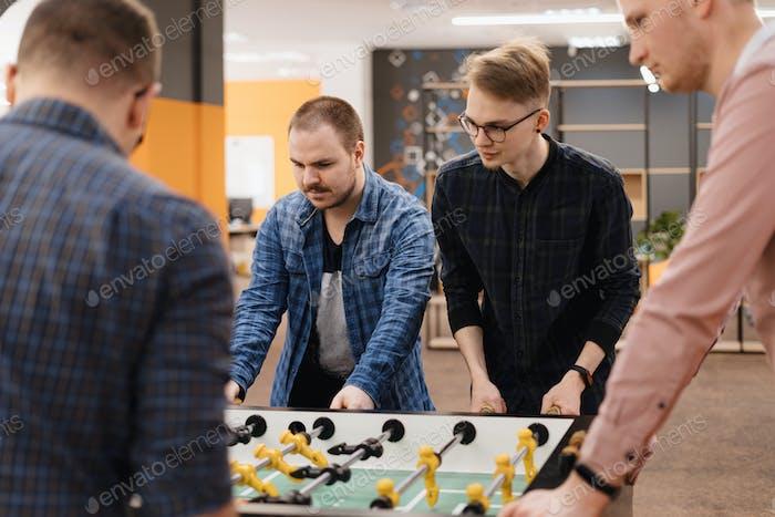 Junge Büroangestellte spielen Tischfußball