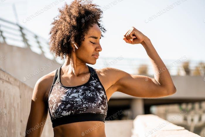 Афро спортсмен женщина сгибает и показывает мышцы.
