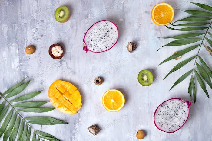 Tropical fruits assortment on a stone light background pattern. Top view. Copy space