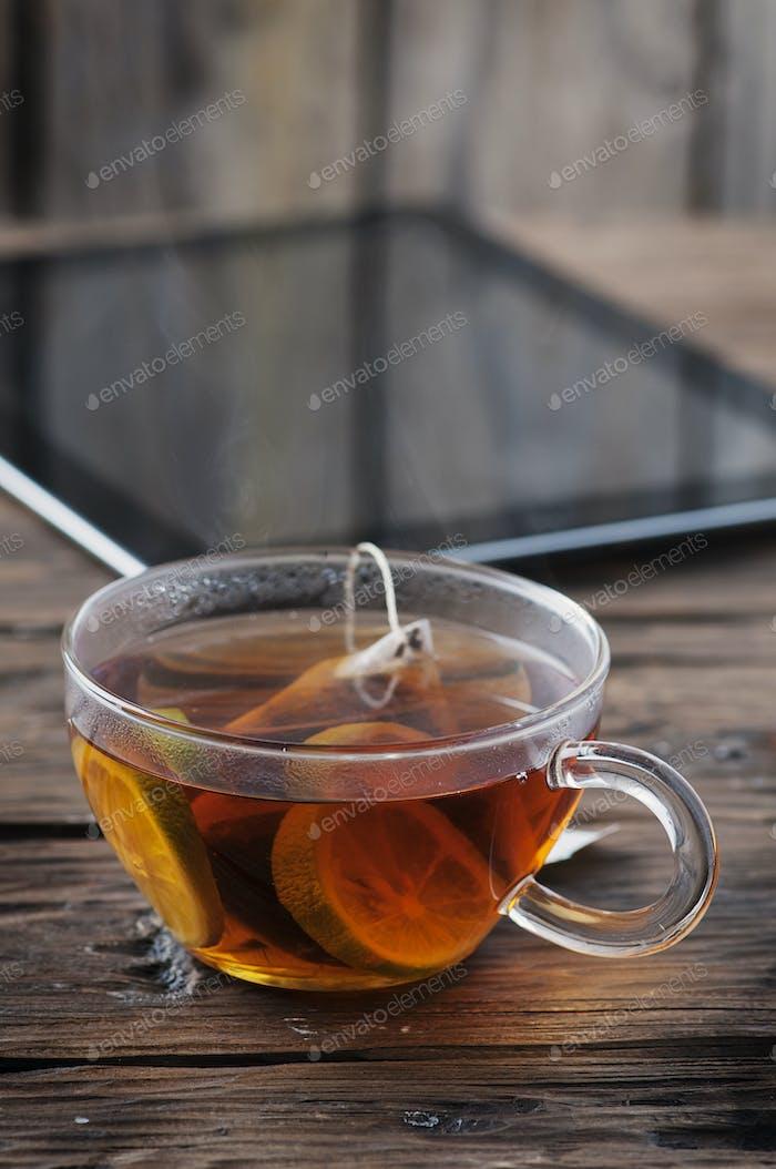 Digitale Tablette und Tasse Tee auf alten Holztisch