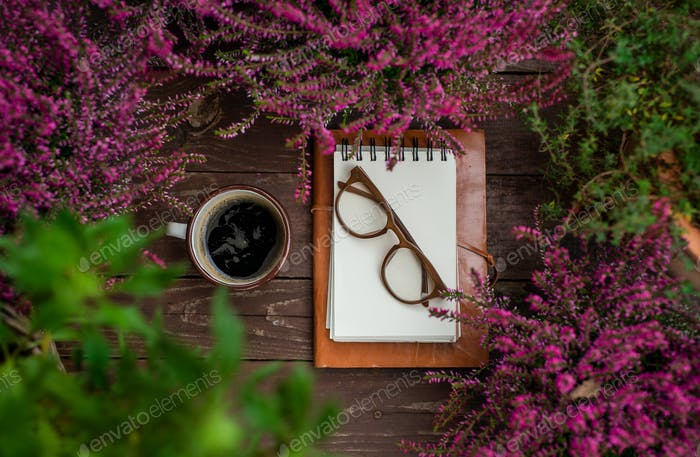 Composition of notepad and coffee on bench outdoors on terrace