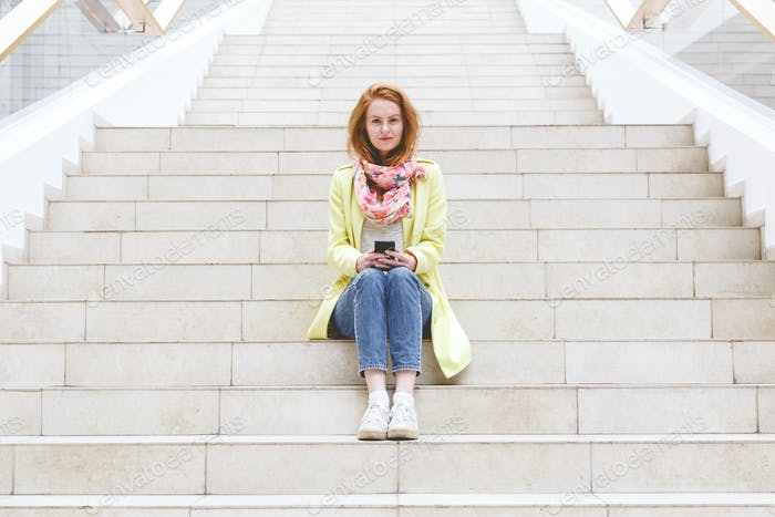 Woman sitting on the stairs and using her smartphone