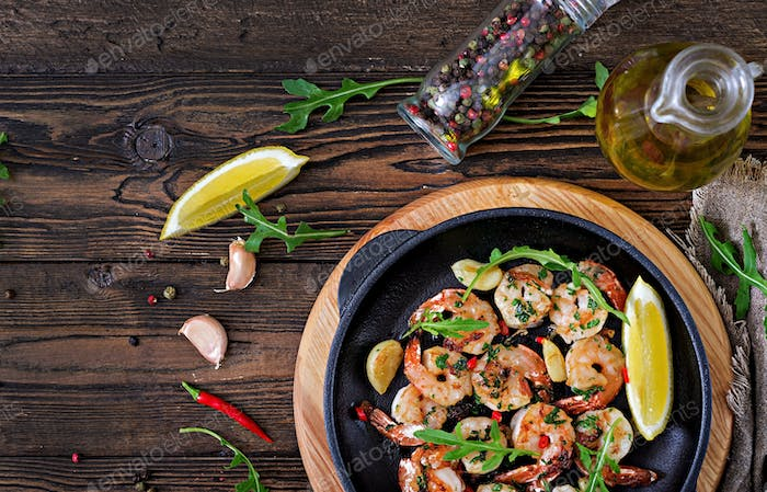 Prawns Shrimps roasted in garlic butter with lemon and parsley on wooden background.