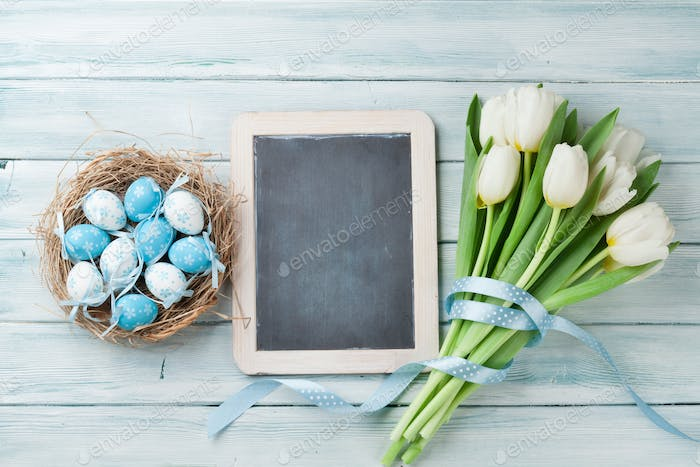 Easter eggs, chalkboard and white tulips
