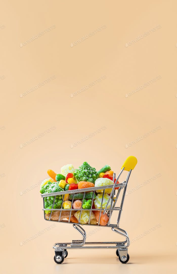 Frozen vegetables assorted on beige, vertical