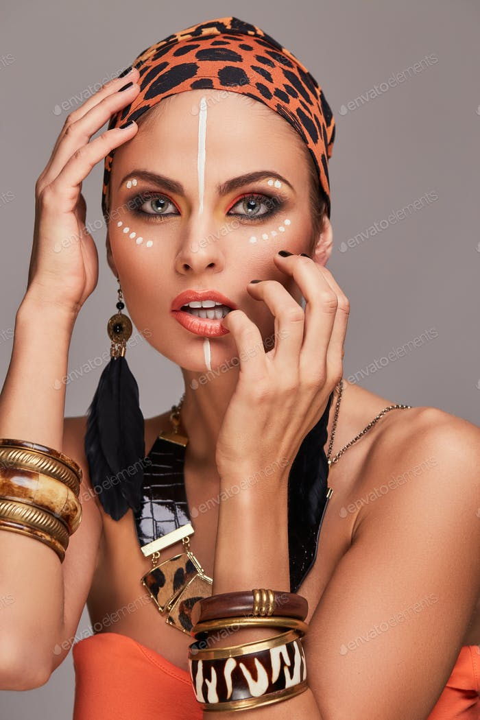 Beautiful caucasian woman with makeup wearing colorful shawl on head and accessories