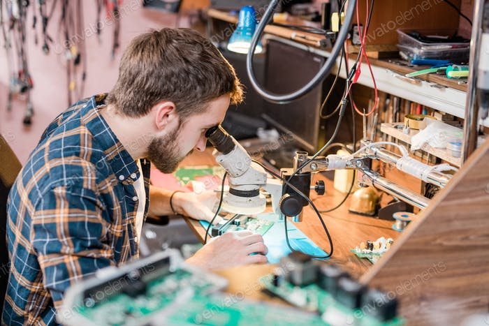 Professional gadget repairman looking in microscope while trying to find problem