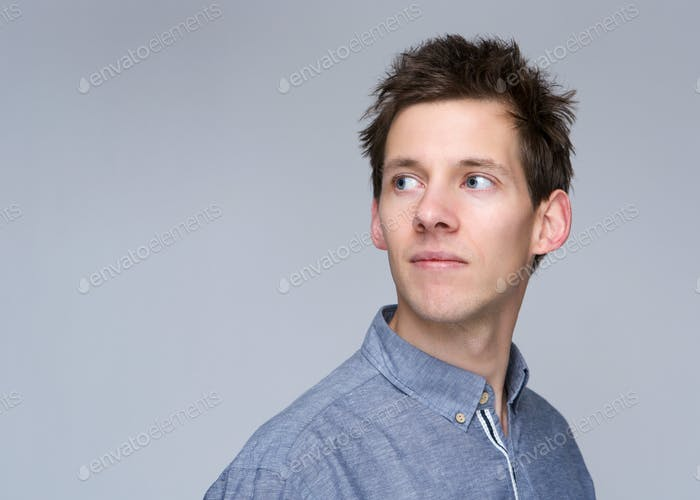 Young man looking away on gray background
