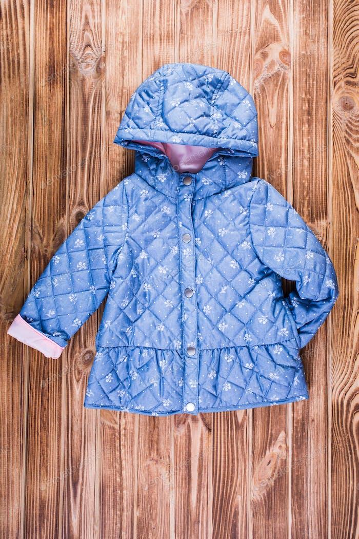 Baby blue warm jacket on wooden background
