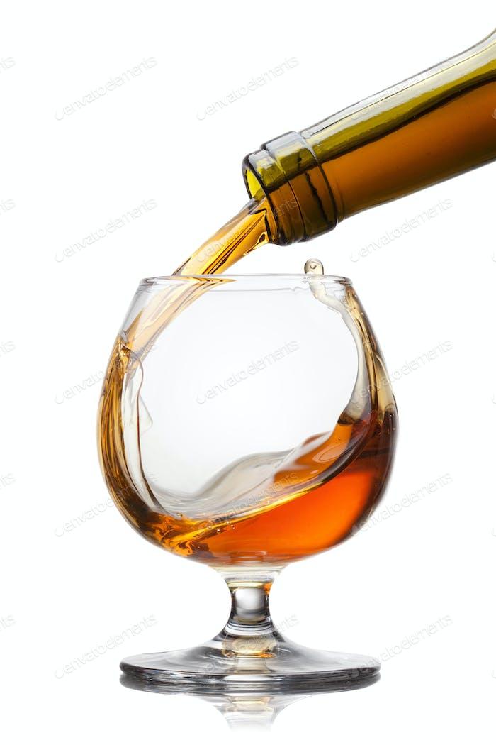 Cognac Gießen in Glas mit Splash isoliert auf weißem Backgrou