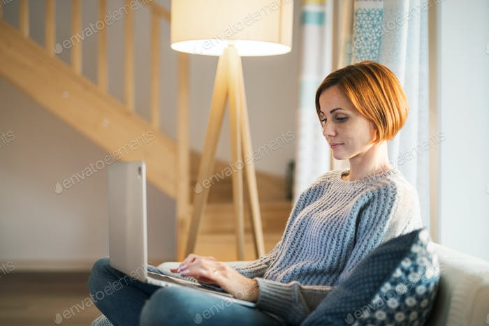 A young woman sitting indoors on a sofa at home, using laptop.