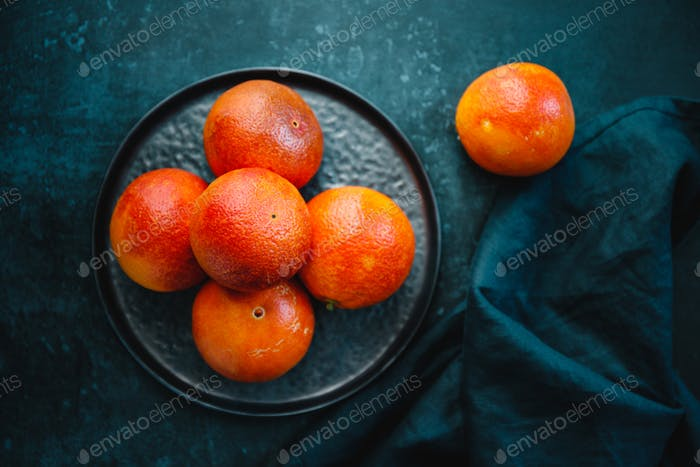 Blood oranges in a plate on a dark blue background