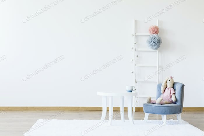 Plush toy on grey chair at white table in minimal child's room i
