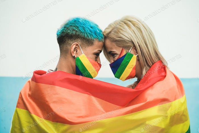 Young couple of lesbian women under lgbt rainbow flag