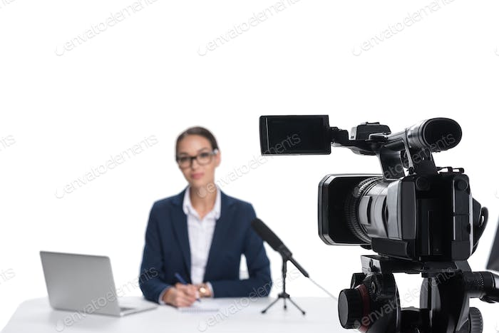 female newscaster sitting at table with laptop and microphone and looking at camera, isolated on