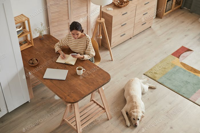 Young Woman Working at Cozy Home Office with Dog