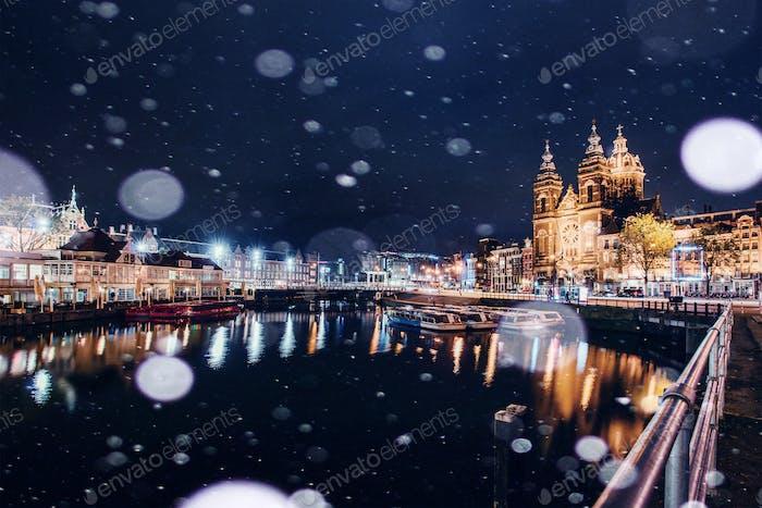 Schöne Nacht in Amsterdam. Nachtbeleuchtung von Gebäuden und Booten in der Nähe des Wassers im Kanal