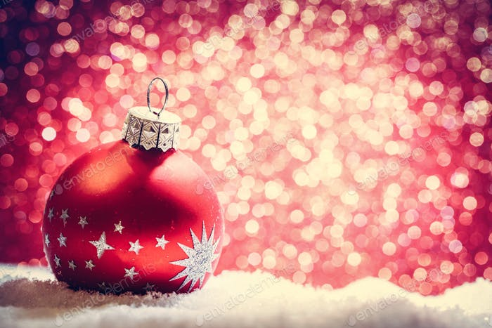 Christmas glass ball in snow. Glitter background