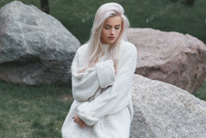 Blonde Hair beautiful female wearing in knitted white sweater