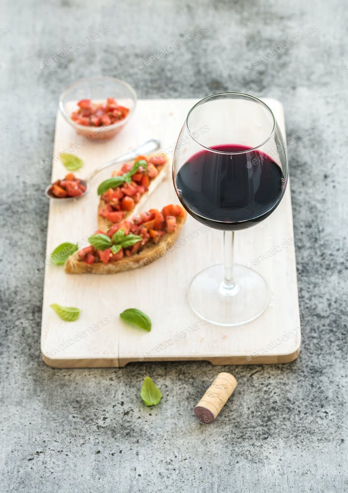 Wine appetizer set. Glass of red wine, brushettas with fresh tomato and basil