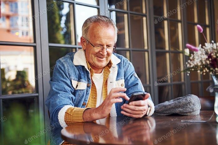 Stilvolle Senior in modischer Kleidung und in Brille sitzt im Café mit Telefon