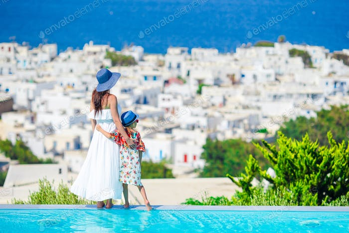 Adorable little girl and young mother in outdoor swimming pool background Mykonos town on Cyclades