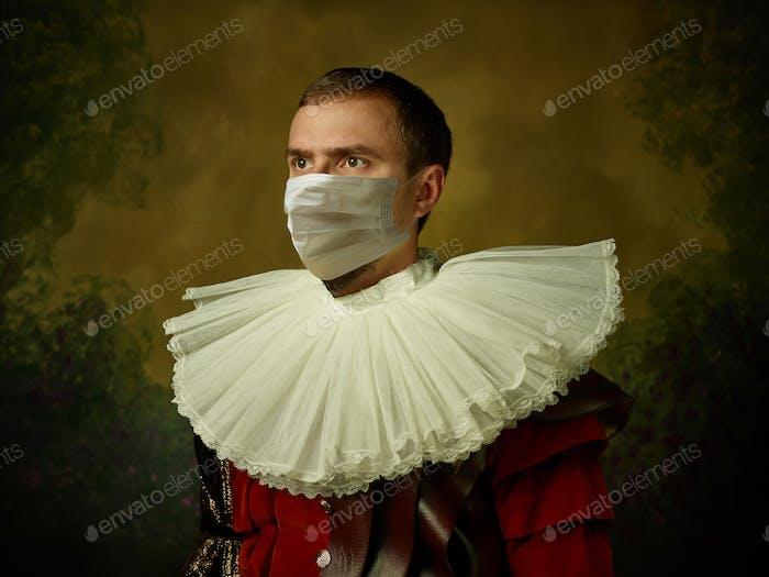 Молодой человек как средневековый рыцарь на темном фоне в защитной маске от коронавируса