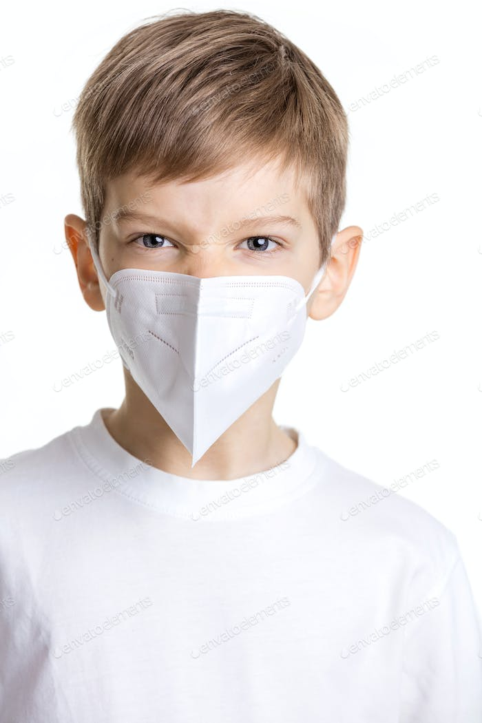 Portrait of young boy in medical mask making angry face over white