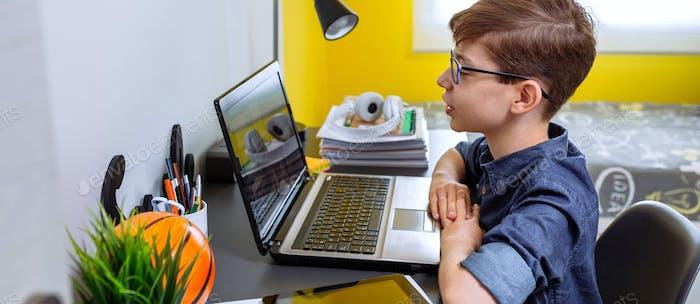 Preteen empfängt Klasse zu Hause mit Laptop aus seinem Schlafzimmer