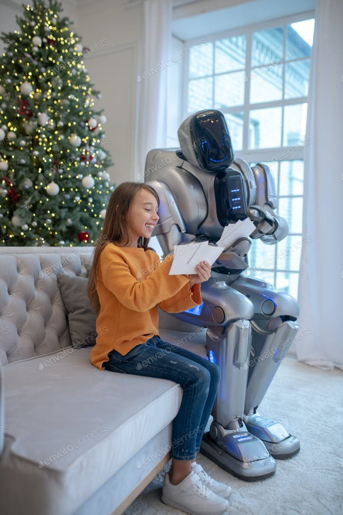 Robot and a cute girl sitting on the sofa