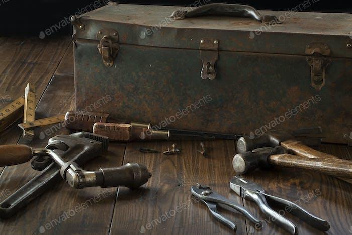 Antike Werkzeuge und Werkzeugkasten auf dunklem Holzoberfläche