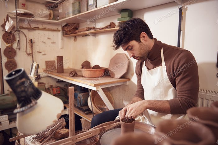Male Potter Shaping Clay For Pot On Pottery Wheel In Ceramics Studio