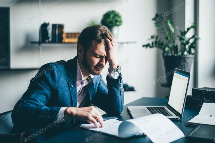 Manager sitting at the desk with laptop, reading important documents with puzzled expression