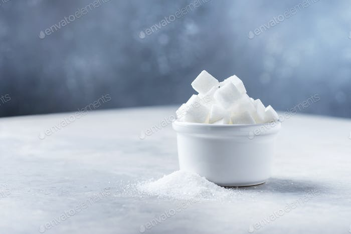 Sugar cubes and grain of sugar