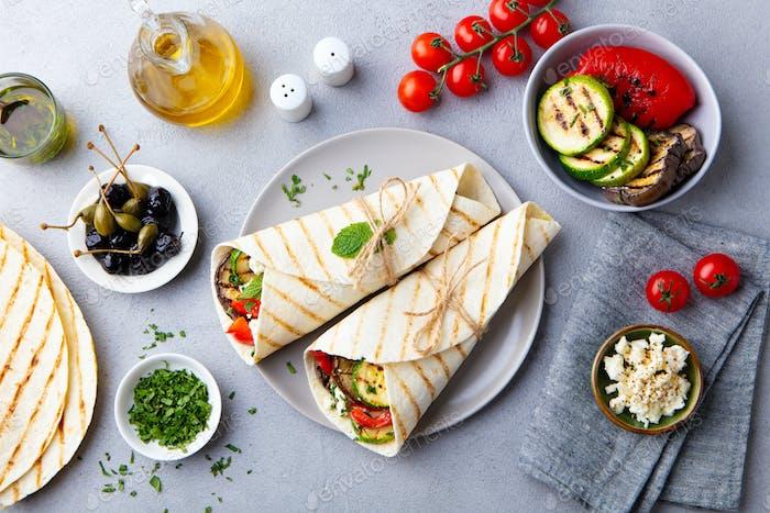 Wrap Sandwich mit gegrilltem Gemüse und Feta-Käse auf einem Teller. Grauer Hintergrund. Draufsicht.