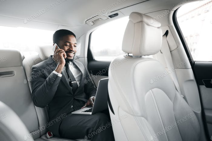 Always available. Young businessman working on laptop in car