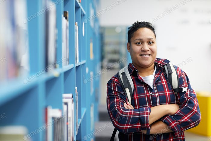 Student posiert in Bibliothek
